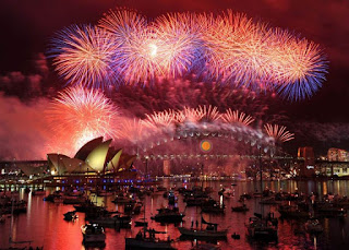 A fireworks display in shades of pink and purple in the harbor of Sydney, Australia. There are black silhouettes of small boars  and the Opera House and bridge in the background.