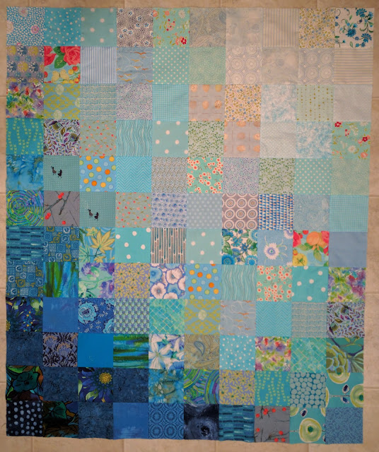 Blue fabric squares shading from white to navy form the background of a Double Vision quilt