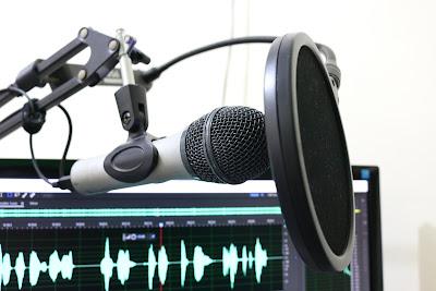Mikrofon, w tle wykres głosu ludzkiego na monitorze