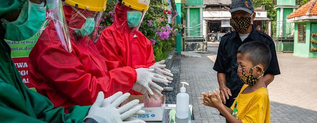 Trabajadores de salud le enseñan a un niño a lavarse las manos. © UNICEF/Fauzan Ijazah