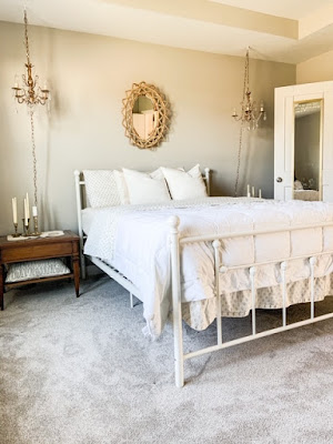 White metal bed with neutral bedding