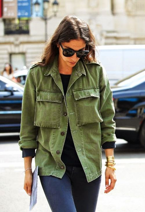 Wearing a Military Jacket Olive Green accessorized with Gold Bracelets and Sunglasses