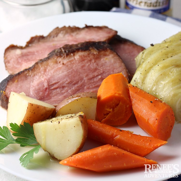 Sliced cottage ham on plate with carrots, cabbage, and potatoes, ready to eat.
