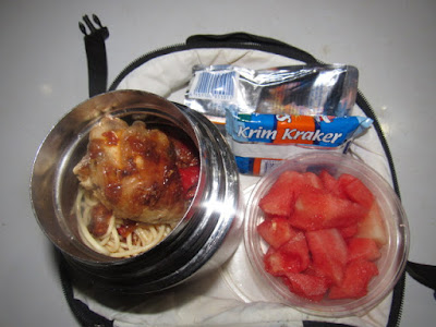 Nigerian school lunchbox meal of spaghetti with stew served with a side of watermelon