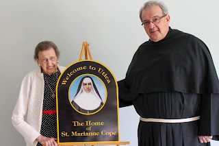 "Honoree Betty Frank and Fr. Christopher with ""Welcome to Utica"" sign"