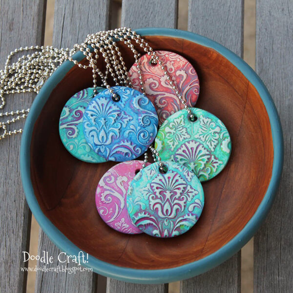 Polymer clay (oven back clay like sculpey or fimo) with stamped impression painted with variegated colors and turned into a pendant necklace