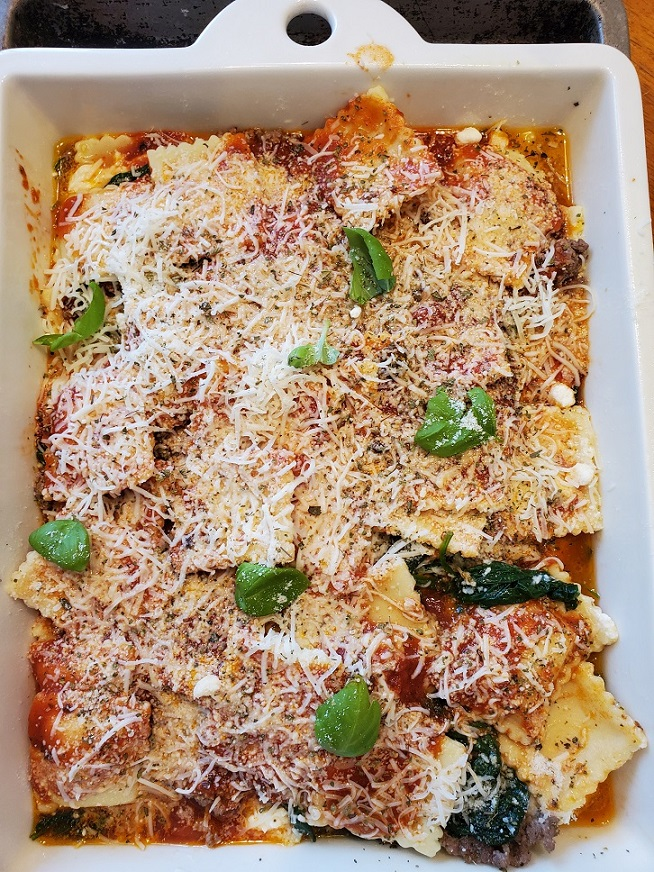 baked ravioli in a casserole with cheese and fresh basil on top