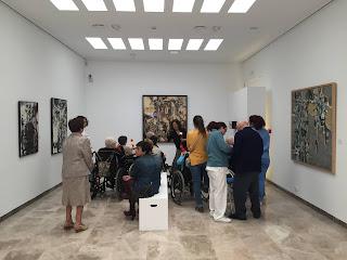 Asistentes de pie, sentados en  banco de la sala y en silla de ruedas contemplando la obra Picador de Antonio Povedano.