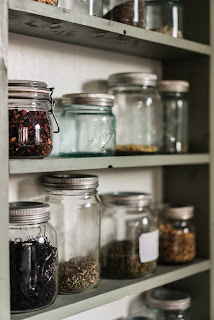 Glass jars with silver lids on gray pantry shelves-no bugs are getting in here.