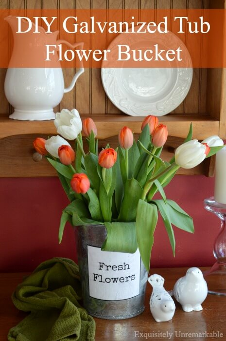 Orange tulips in metal flower vase with printable flowers label on front, sitting on wooden table next to green towel