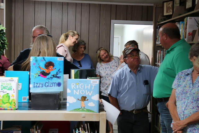 A large group of people are standing around talking. They are crammed into a library and children's books are arranged on the tops of bookshelves.