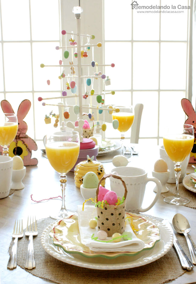 a colorful table to celebrate Easter with rabbits, yellow plates, orange juice