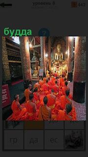 В зале храма сидят монахи и молятся, статуя будды в центре