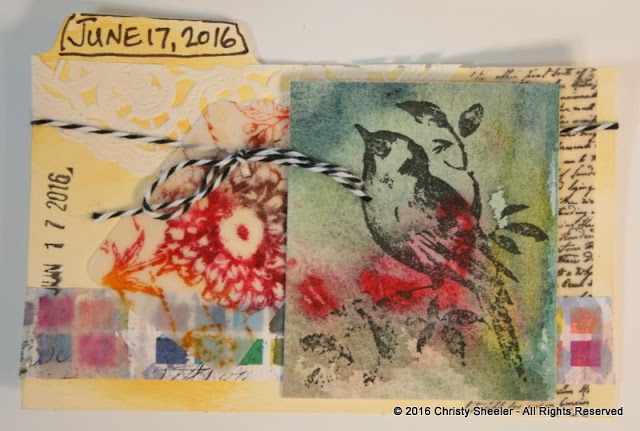 ICAD June 17, A collage on pale yellow gesso and watercolor background.  Stamped script, flower and bird.
