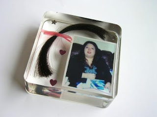 A lock of hair and photograph preserved within a paperweight