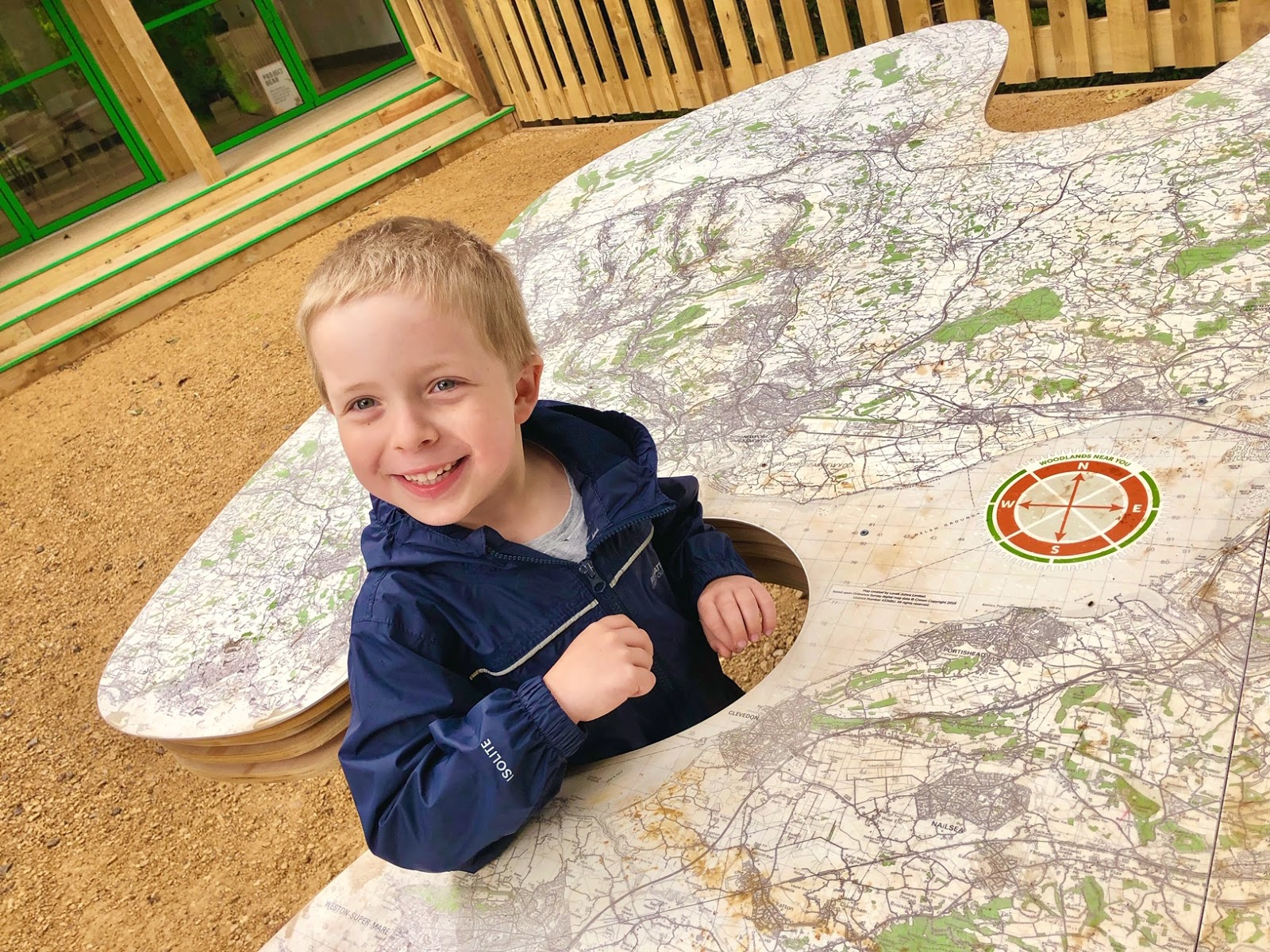 a boy smiling whilst standing inside a large map installation