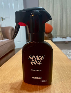 A black spray bottle with a red catcher lever at the bottom of the spray part with a black domed label on the front that says Space Girl in large white font with Body Spray in smaller white font with #LushLabs in smaller white font on a large rectangular light brown tape with a light grey rectangular sofa in the background and a light cream rectangular shaped door on a bright background