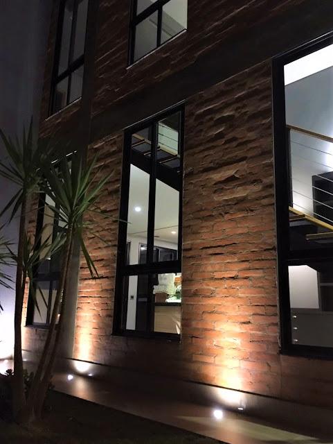 Efeitos luminosos enriquecem o visual da sala de estar e jantar quando vistas a partir de um jardim externo em períodos noturnos *.