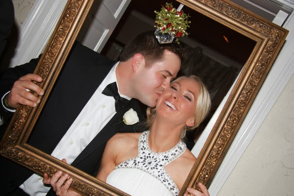 A bridesmaid and groomsmen share a precious cheek kiss under the mistletoe
