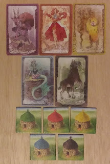 On top are the five colour cards from Fae: Purple (the art showing a goat man - the Pooka), Red (a hovering woman with a ball of flame in her hand), Yellow (A tree person - an dryad), blue (a mer creature), and black (a watery horse - the kelpie). Below that are the five tiles from Clans, which have identical art displaying a round stone hut with conical thatched roof, the roofs being in different colours: green, red, yellow, blue, and black.