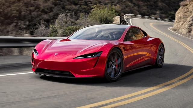 automóvil deportivo tesla roadster color rojo en marcha en la carretera