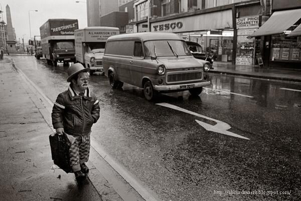 A crying clown walking on the streets of London on a rainy day, c. 1975