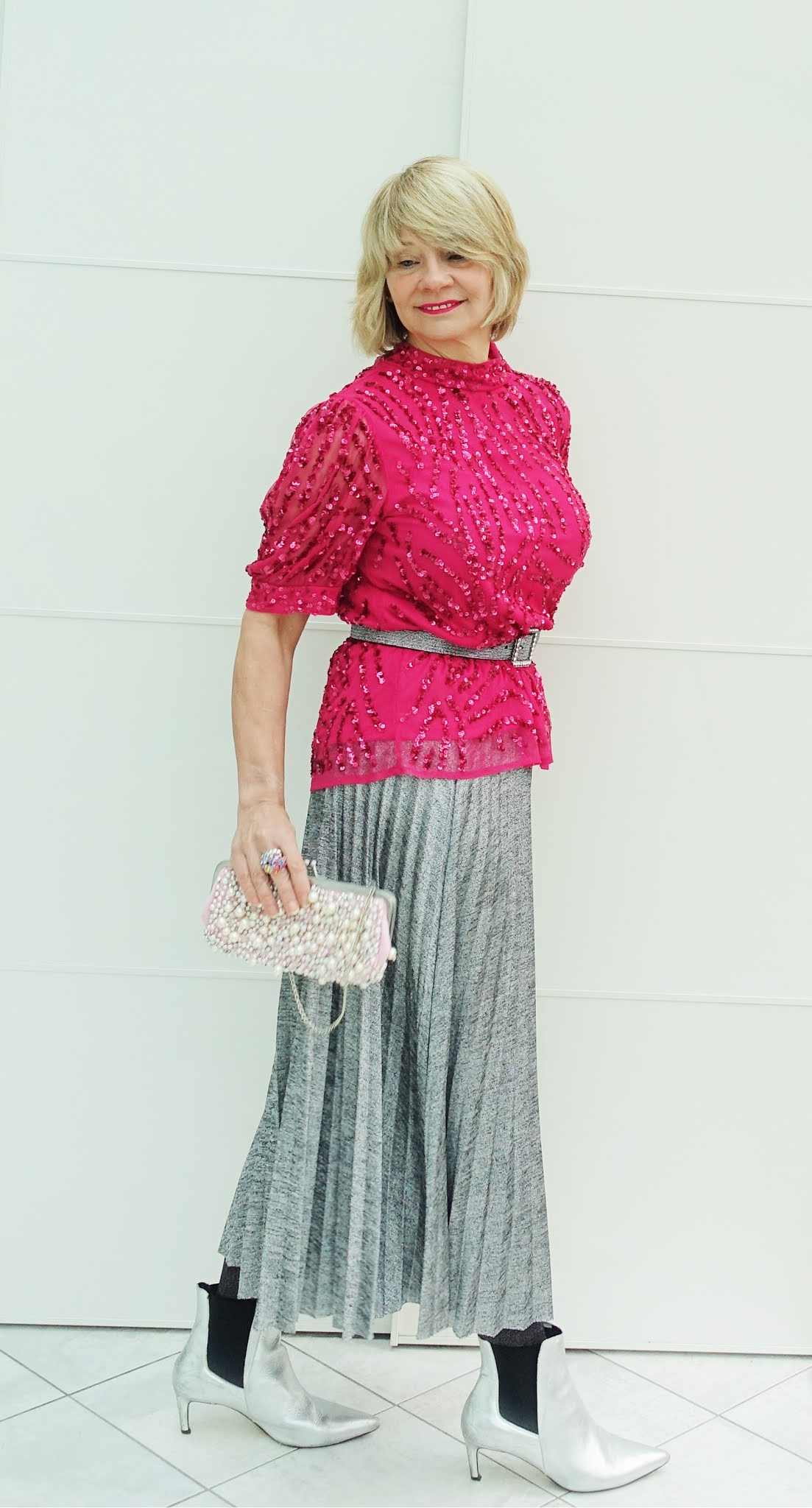 Gail Hanlon from Is This Mutton in a sparkly sequin top for Christmas with a silver pleated skirt and silver boots