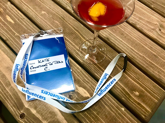 "A lanyard saying ""Influencer"" next to a cocktail on a wooden table"