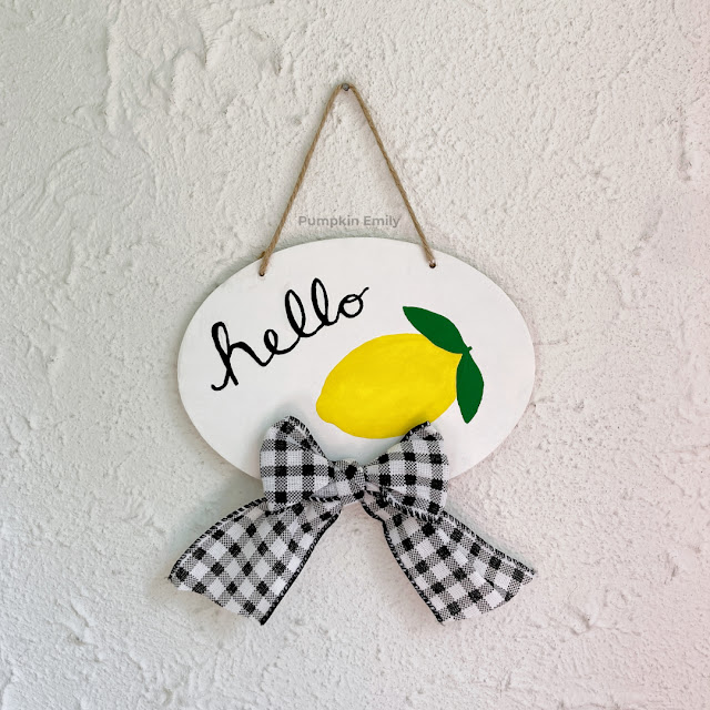 A lemon wood sign with a bow.