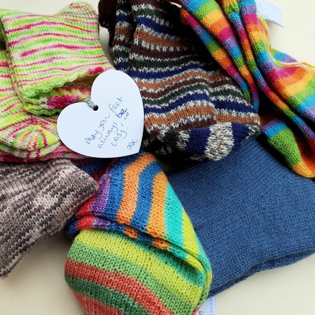 Multi-coloured socks in a pile.  The tag on one of the socks is visible