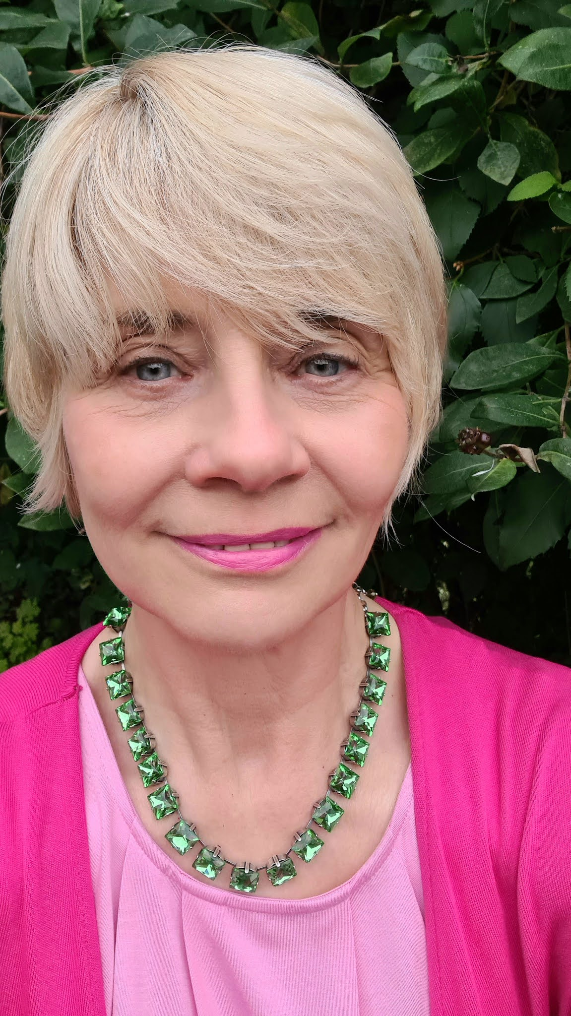 Head shot of Gail Hanlon from over 50s blog Is This Mutton in fuchsia pink with a green Anna Wintour necklace