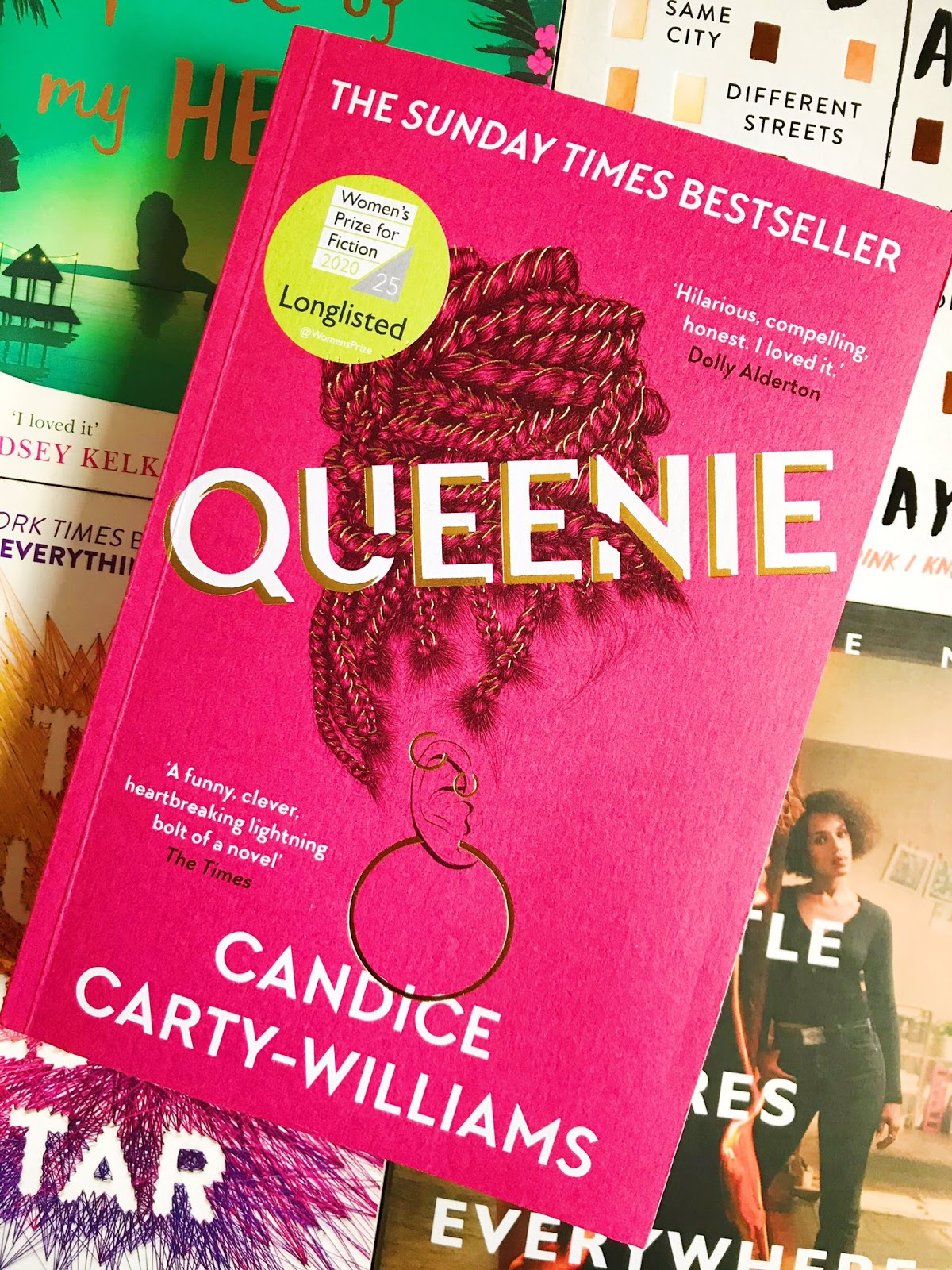 Queenie by Candice Carty-Williams. Flatlay. Book on top of 4 other books