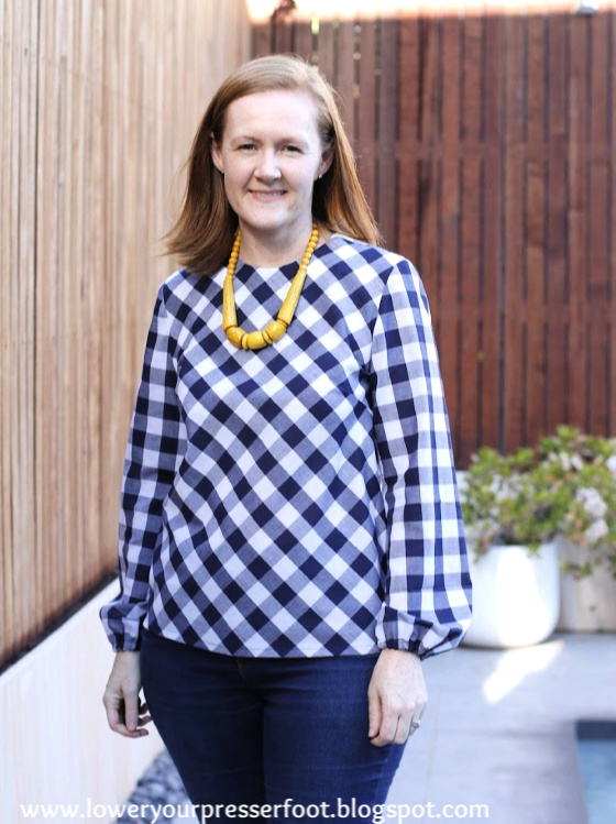 woman posing in a navy blue gingham top worn with a yellow necklace beside a timber fence