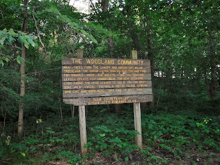 "a wooden sign with golden letters provides information about the ""woodland community"" at Bacon Creek Park"