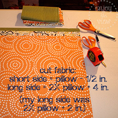 orange print fabric, measuring tape, scissors on a table