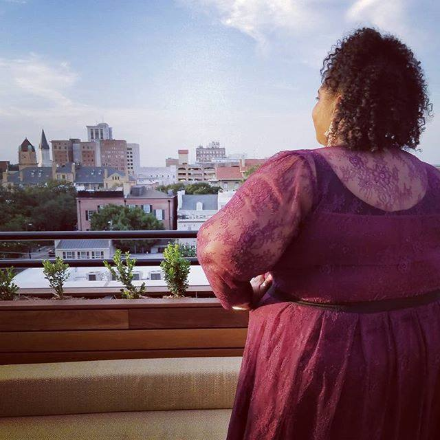 Kirsten, The Low Country Socialite, is standing on a rooftop in Savannah, Georgia.  She is wearing a wine colored dress from Eloquii with lace detailing.  She has her back turned towards the camera and she is looking out onto the skyline.  Her hair is curly and you cannot see her face.