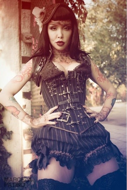 woman wearing menswear inspired brown striped tweed corset with lace up back, matching striped tweed bloomers/shorts and a fascinator with black lace top thigh high stockings