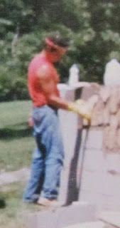 Man in red sleeveless shirt and jeans wearing a red bandana fitting stones into a wall.