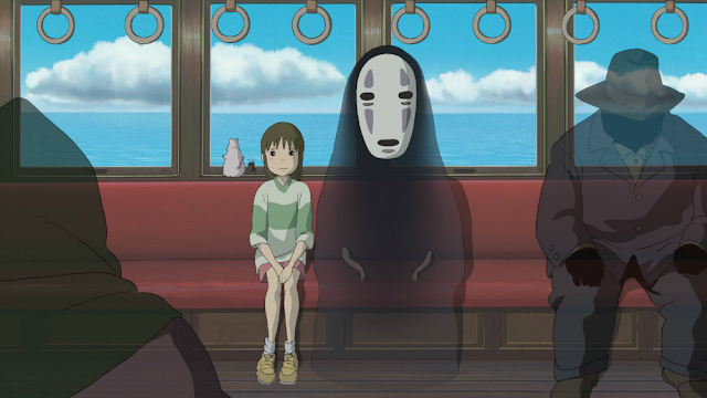 A scene from Studio Ghibli movie Spirited away where a girl sits inside a train behind a masked ghost wearing black cloak and other souls