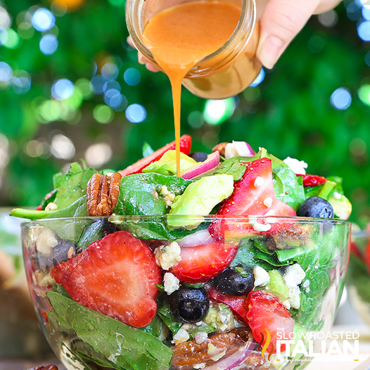 pouring dressing over spinach salad with strawberries