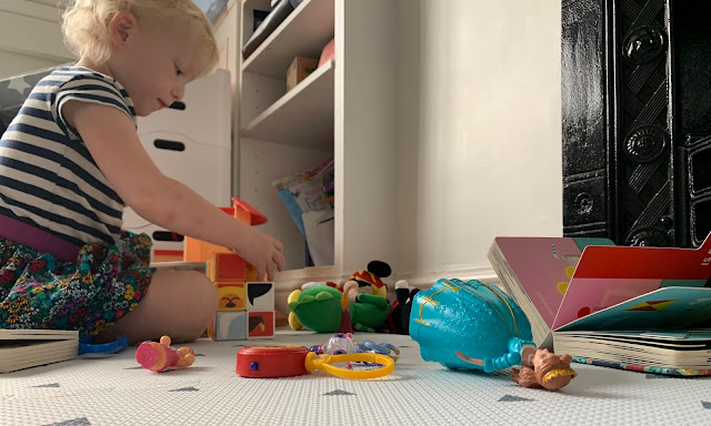 Toddler surrounded by toys and books in the living room