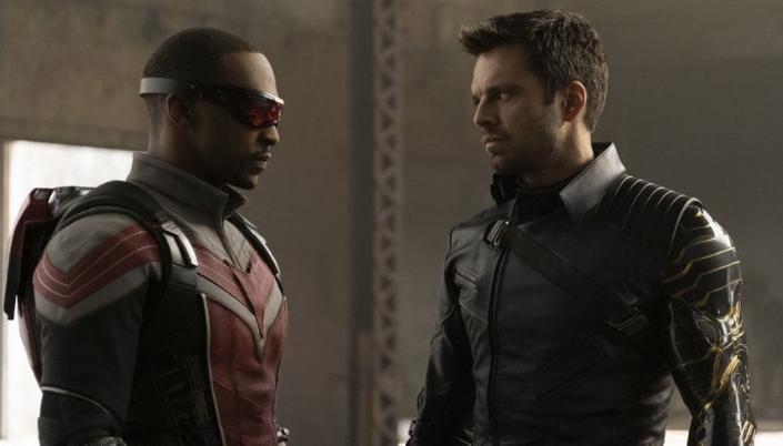 Imagem: os personagens Falcão e o Bucky, um homem negro em um uniforme vermelho com cores prateadas e um óculos vermelho e Bucky, um homem branco de cabelos pretos curtos e barba aparada, um traje escuro de couro e o braço biônico.