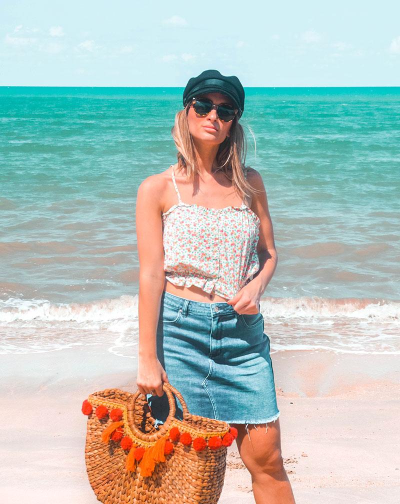 summer outfit denim skirt floral crop top baker boy hat basket bag on beach