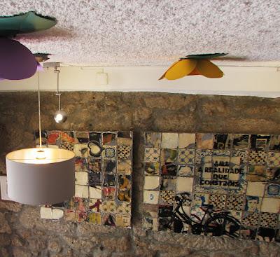 Quadros na parede, uma luminária e alguns enfeites pendurados no tecto