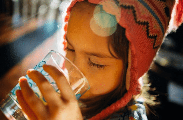 kid drinking water in a glass