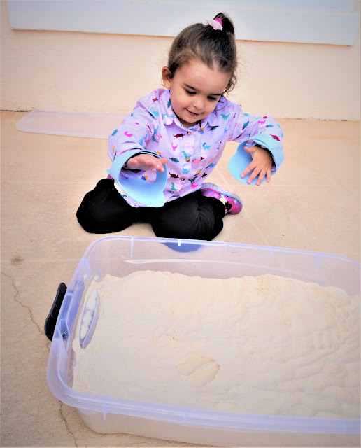 Little girl wears foam shoes on her hands to make a deer print in the sand.