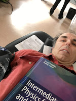 A selfie of me giving blood, with Intermedaite Physics for Medicine and Biology balanced on my chest.
