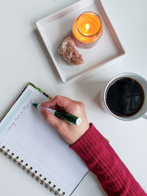 A lined notebook on a white table with a hand writing Coming Back To Blogging with a pen next to a cup of coffee and an orange candle and a crystal on a white square tray.