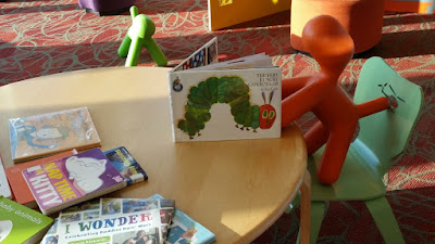 toy puppy reading The Hungry Caterpillar at library table
