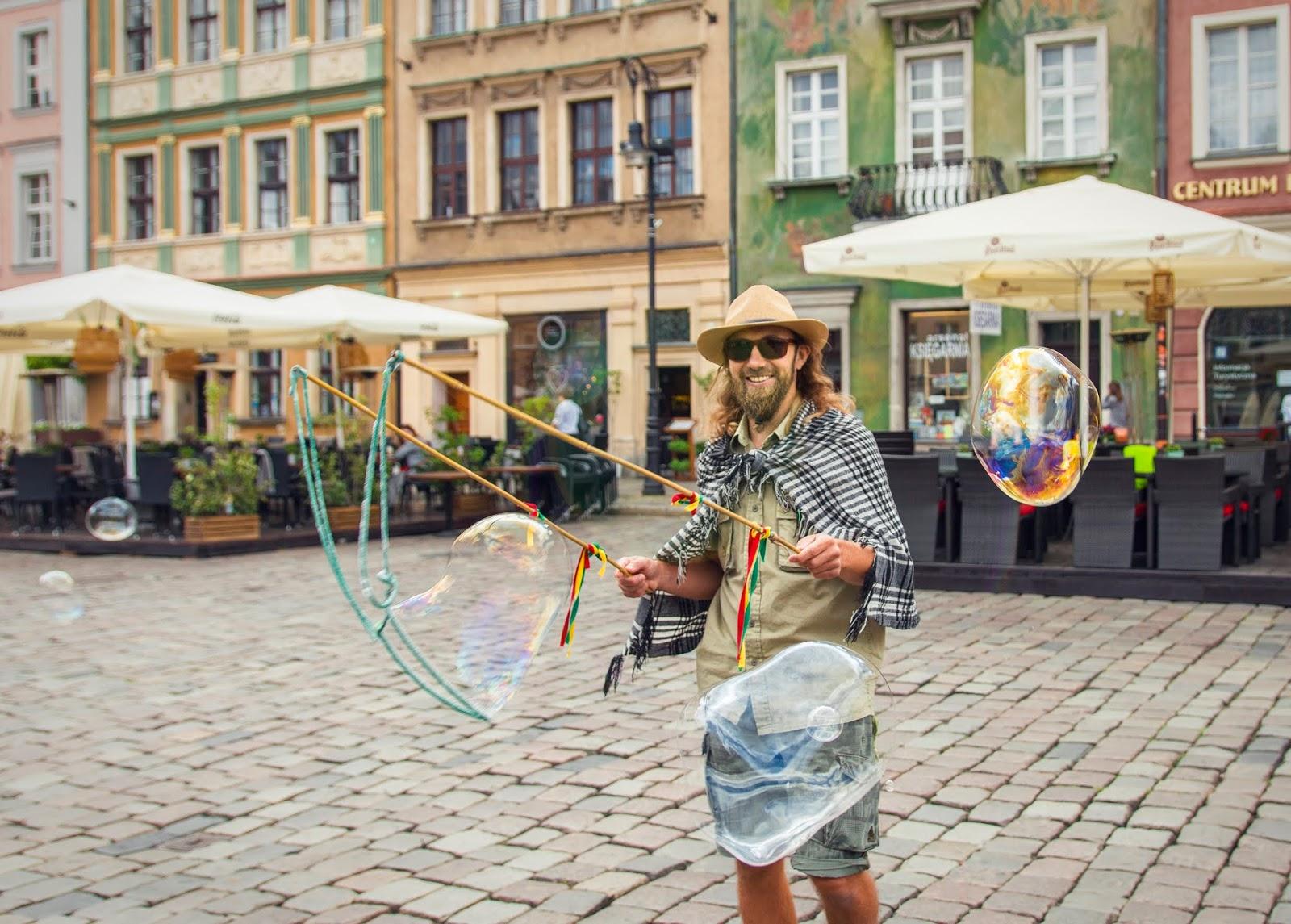 Na zdjęciu widać uśmiechniętego mężczyznę w kapeluszu, który puszcza bańki mydlane. w tle zabytkowe kamieniczki otaczające Stary Rynek w Poznaniu z restauracyjnymi ogródkami